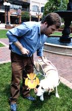 Immagine di un non vedente alla ricerca di pokemon con il suo cane guida